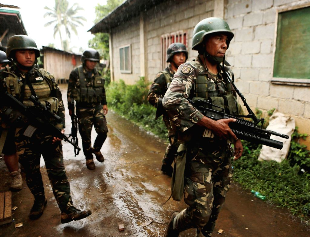 Soldiers walk under the rain as they search for residents still trapped in their homes in Marawi City in Lanao Del Sur Province, the Philippines, June ...