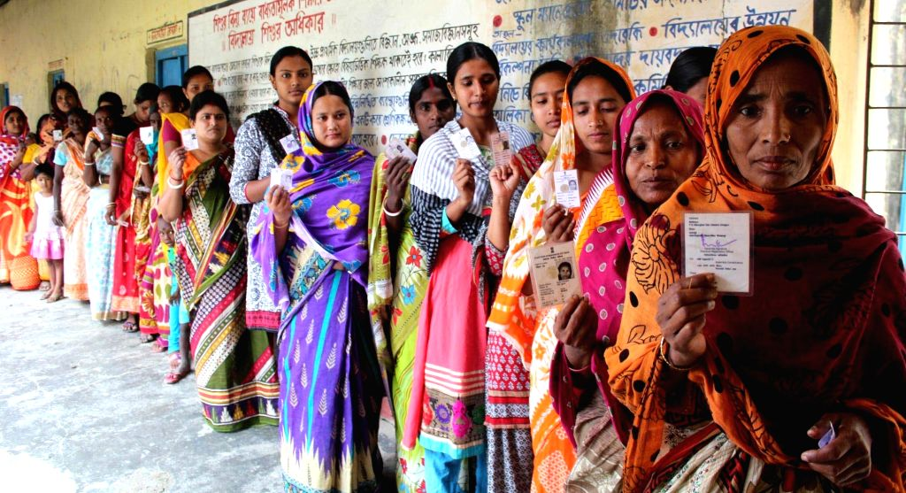 South Dinajpur: Women show their voter's identity card as they queue up to cast their votes during the third phase of West Bengal Legislative Assembly polls in South Dinajpur district of West Bengal ...