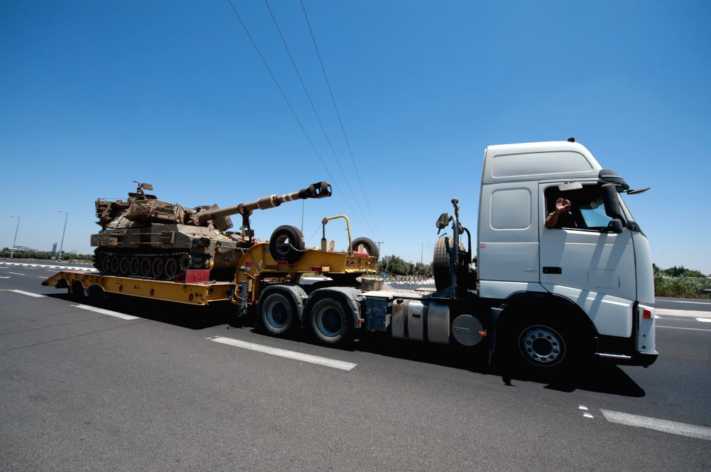 A truck carrying an Israeli army's armored vehicle runs toward the border areas between southern Israel and Gaza, on July 8, 2014. Israel's security cabinet ...
