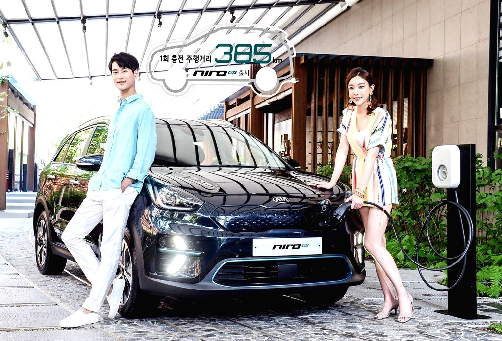 South Korea: Models stand next to the Niro EV all-electric model, manufactured by Kia Motors Corp., South Korea's second-biggest carmaker by sales, in this undated photo released by the carmaker on ...