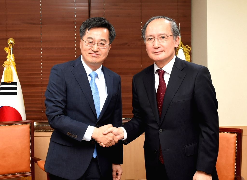 South Korea's Finance Minister Kim Dong-yeon (L) shakes hands with Japanese Ambassador to Seoul Yasumasa Nagamine during a meeting at the government complex in Seoul ion June 26, 2017. (Photo ... - Kim Dong