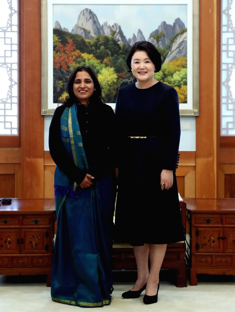 South Korea's first lady Kim Jung-sook (R) poses for a photo with Indian Ambassador to South Korea Sripriya Ranganathan during their meeting at the presidential office Cheong Wa Dae in Seoul ...