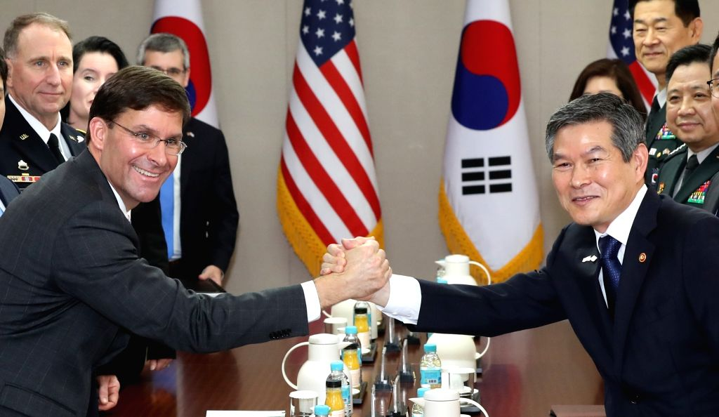 South Korean Defense Minister Jeong Kyeong-doo (R) and U.S. Secretary of Defense Mark Esper clasp hands during their talks at the defense ministry in Seoul on Aug. 9, 2019. - Jeong Kyeong