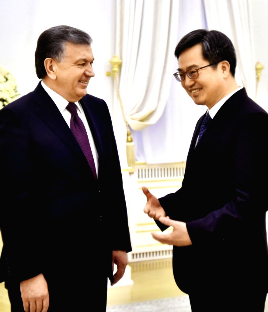 South Korean Finance Minister Kim Dong-yeon (R) talks with Uzbek President Shavkat Mirziyoyev during their meeting at the presidential palace in Tashkent on Feb. 13, 2018, in this photo ... - Kim Dong