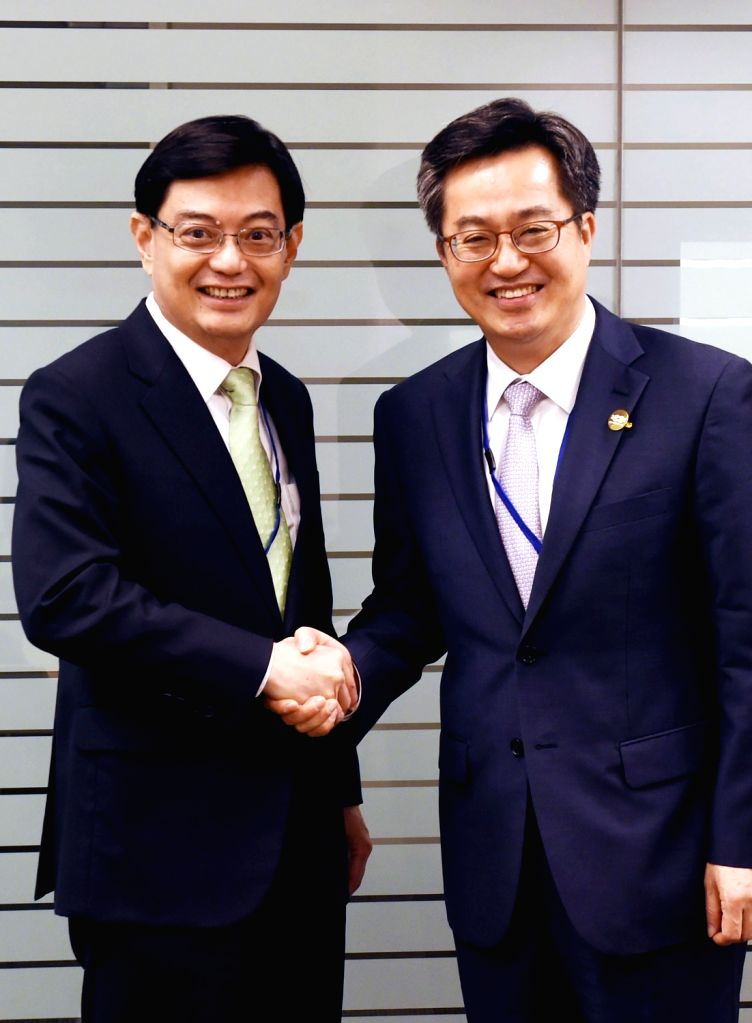 South Korean Finance Minister Kim Dong-yeon (R) and his Singaporean counterpart Heng Swee Keat pose prior to their talks on the sidelines of the annual meeting of the IMF and the World ... - Kim Dong