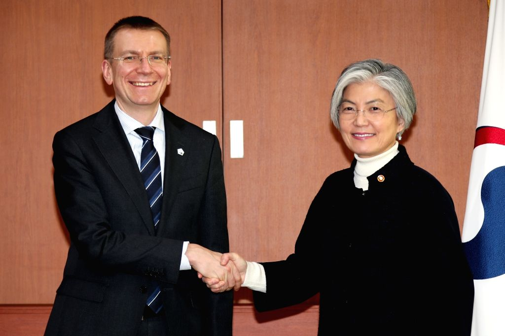 South Korean Foreign Minister Kang Kyung-wha (R) poses for a photo with her Latvian counterpart Edgars Rinkevics during their meeting at her office in Seoul on Feb. 14, 2018. - Kang Kyung