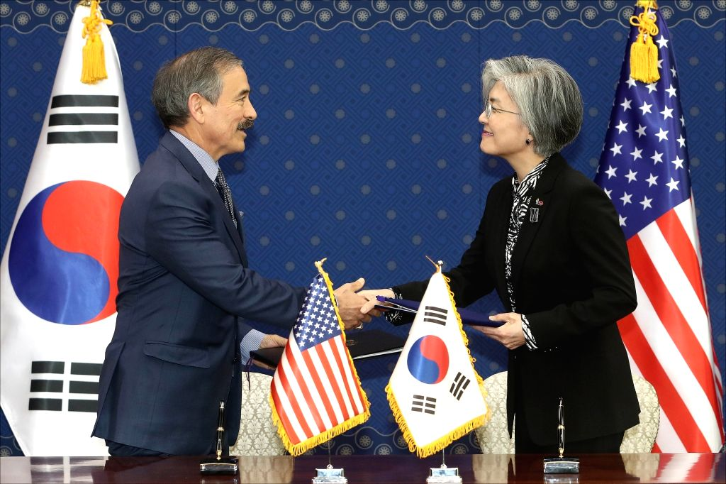 South Korean Foreign Minister Kang Kyung-wha (R) shakes hands with U.S. Ambassador to South Korea Harry Harris during a ceremony at the Foreign Ministry in Seoul on March 8, 2019, to sign the ... - Kang Kyung