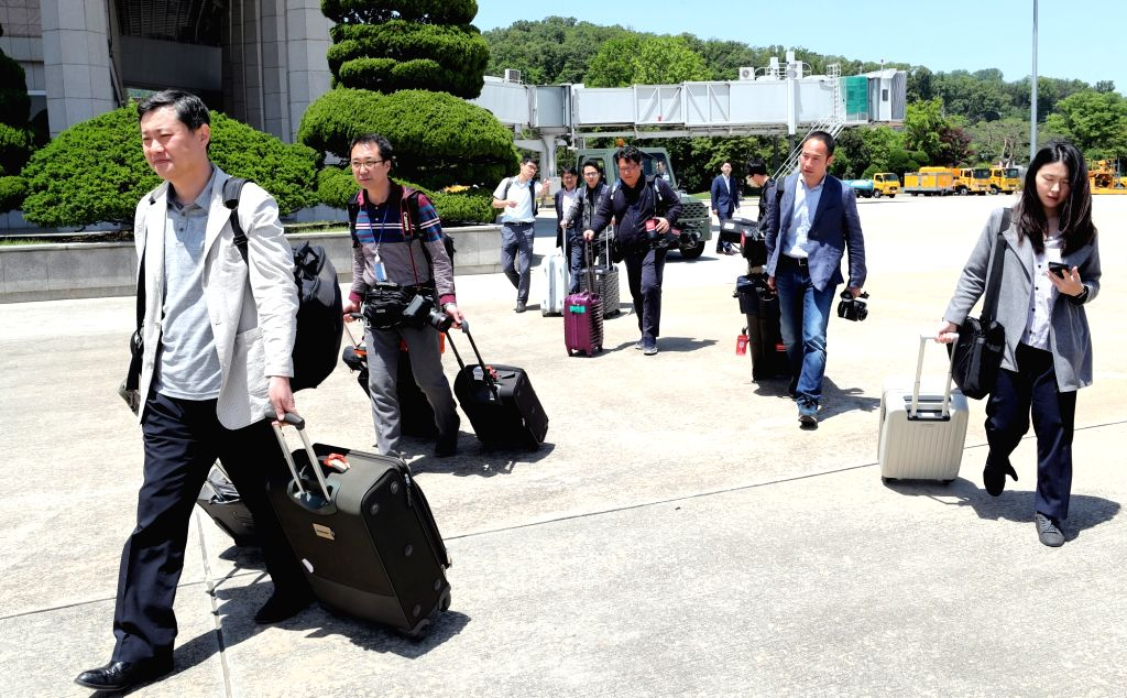 South Korean journalists head to a plane at Seoul Airport, just southeast of Seoul, on May 23, 2018, to go to North Korea where they will cover the dismantlement of the North's key nuclear ...