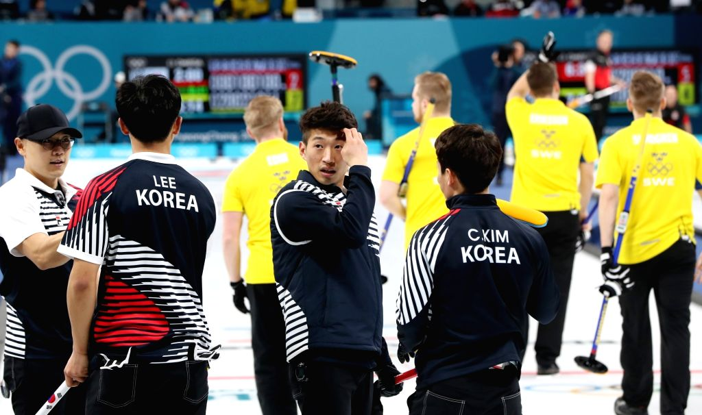 South Korean men's curling team members wrap up their PyeongChang Winter Olympics match against Sweden at Gangneung Curling Centre in the games' sub-host city of Gangneung, east of Seoul, ...