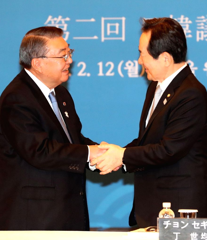 South Korean National Assembly Speaker Chung Sye-kyun (R) shakes hands with Japan's House of Representatives Speaker Tadamori Oshima during a meeting in Seoul on Feb. 12, 2018. - Chung Sye