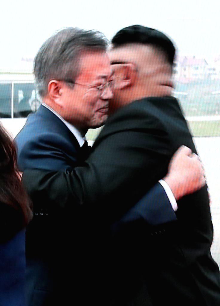 South Korean President Moon Jae-in (L) and North Korean leader Kim Jong-un embrace as they greet each other at Pyongyang International Airport on Sept. 18, 2018, in this image from TV live ...