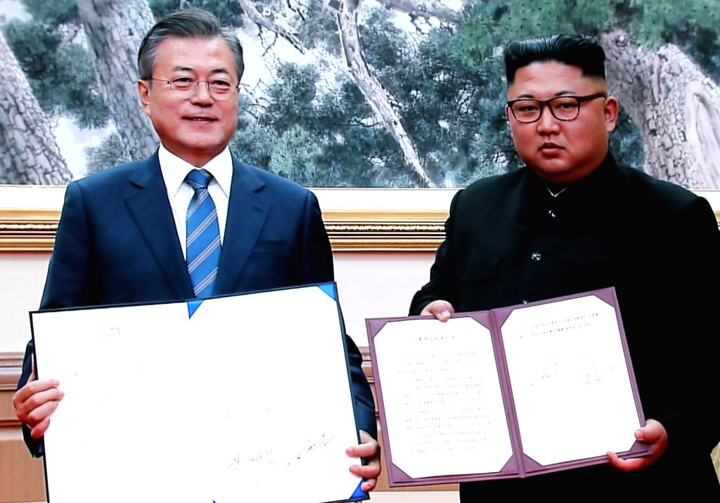 South Korean President Moon Jae-in (L) and North Korean leader Kim Jong-un hold up their summit agreement after their second round of talks in Pyongyang on Sept. 19, 2018, in this image ...