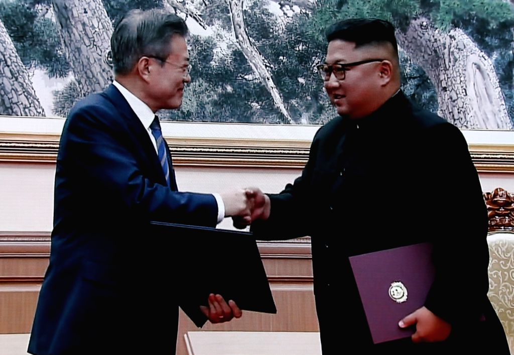 South Korean President Moon Jae-in (L) and North Korean leader Kim Jong-un shake hands after signing their summit agreement following a second round of talks in Pyongyang on Sept. 19, ...