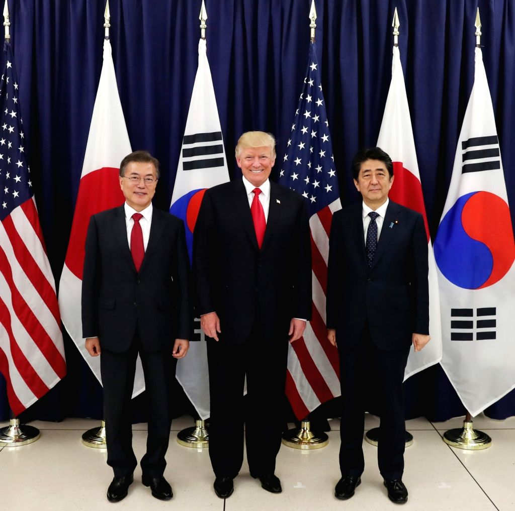 South Korean President Moon Jae-in (L), U.S. President Donald Trump and Japanese Prime Minister Shinzo Abe pose for the camera before a three-way meeting at the U.S. consulate in Hamburg on ... - Shinzo Abe