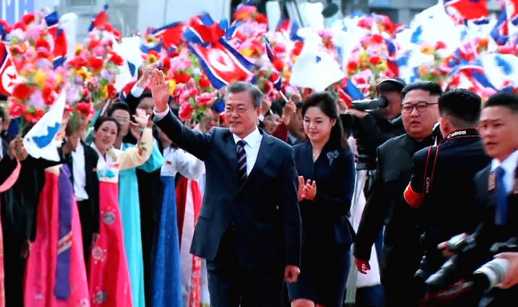 South Korean President Moon Jae-in (L), walking side by side with North Korean leader Kim Jong-un (R), waves to the welcoming crowd at Pyongyang International Airport on Sept. 18, 2018, in ...