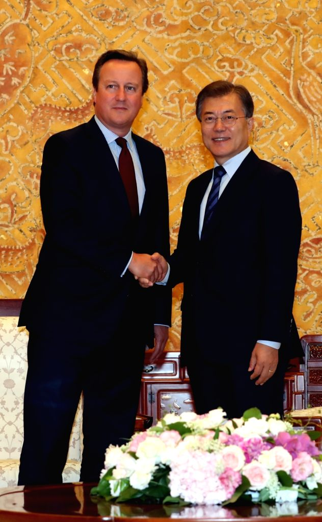 South Korean President Moon Jae-in (R) and former British Prime Minister David Cameron pose for a photo during their meeting at the presidential office Cheong Wa Dae in Seoul on July 4, 2017. - David Cameron