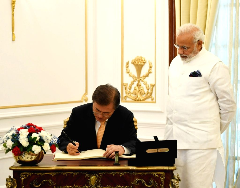 South Korean President Moon Jae-in signs the visitors' book of Hyderabad House as Prime Minister Narendra Modi looks on, in New Delhi on July 10, 2018. - Narendra Modi
