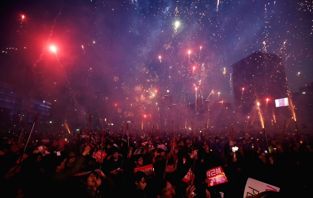 South Korean protesters shoot fireworks to celebrate the ouster of President Park Geun-hye at Gwanghwamun Square in Seoul on March 11, 2017, one day after the Constitutional Court's ruling to ...