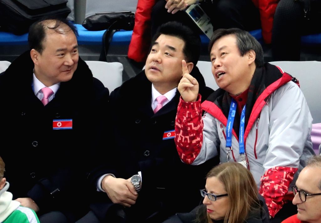 South Korean Sports Minister Do Jong-hwan (R) and his North Korean counterpart Kim Il-guk (C) talk each other while watching the skating pairs short program at Gangnueng Ice Arena in ... - D