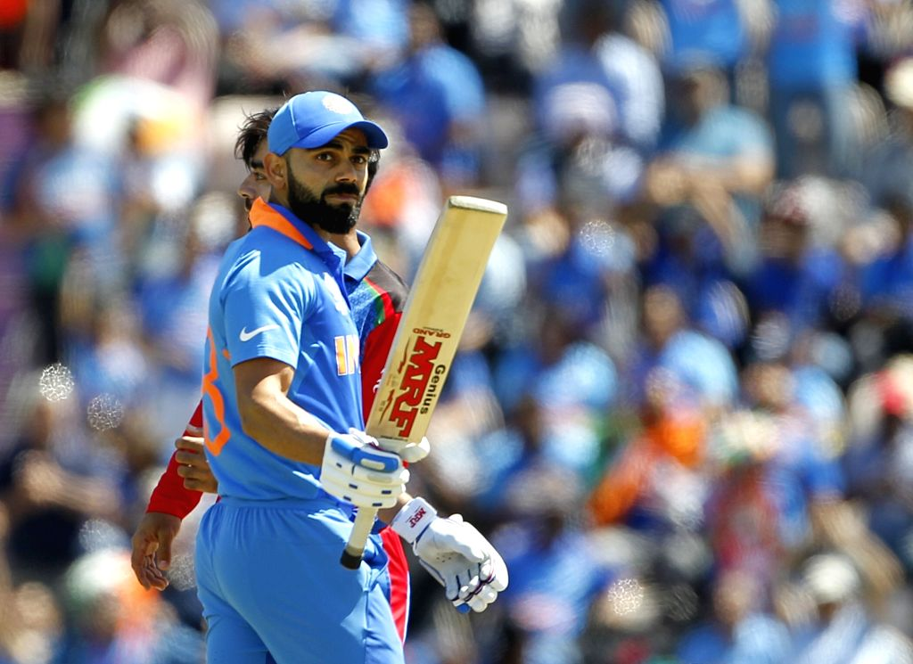 Southampton: India's Virat Kohli celebrates his half century during the 28th match of World Cup 2019 between India and Afghanistan at The Rose Bowl in Southampton, England on June 22, 2019. (Photo: Surjeet Yadav/IANS) - Virat Kohli and Surjeet Yadav