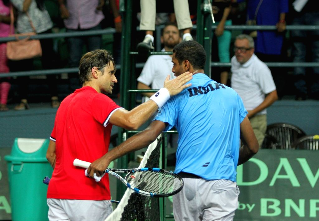 Spain's David Ferrer with  Ramkumar Ramanathan of India during Davis Cup World Group Play-off match at RK Khanna Tennis Stadium in New Delhi on Sept 18, 2016. Spain won.