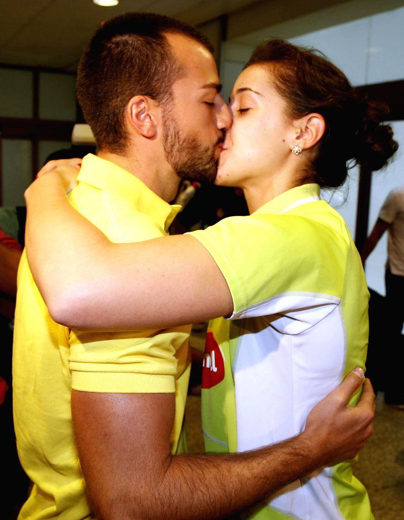 Spanish badminton world champion Carolina Marin (R) kisses her boyfriend (L) as she arrives at Adolfo Suarez Barajas in Madrid, Spain, on 18 August 2015. Carolina Marin won the World Championships in ...