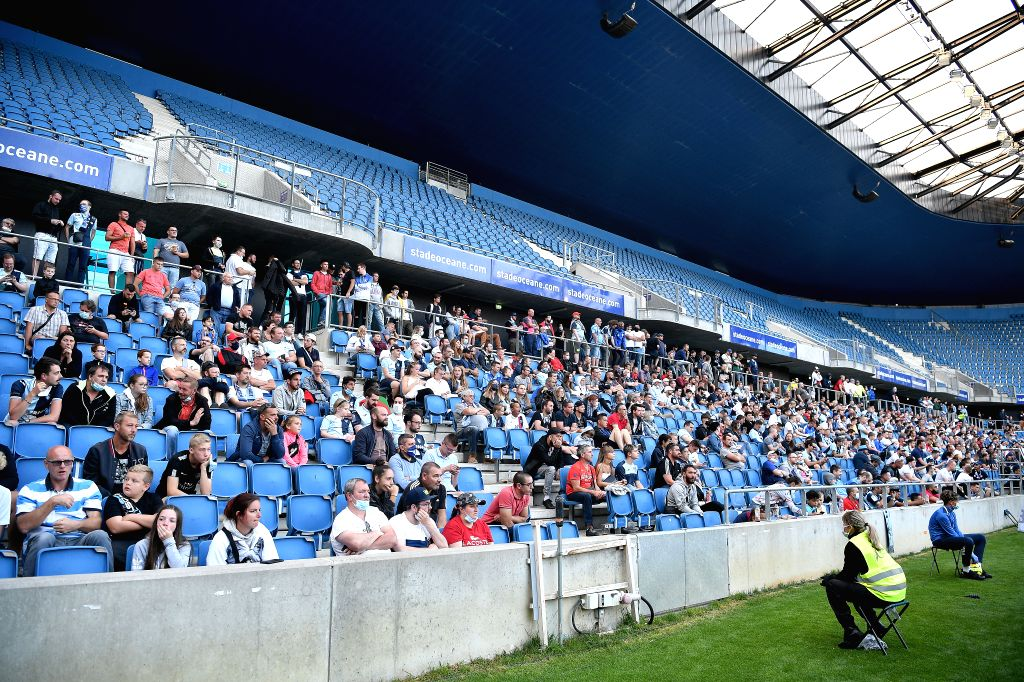 Spectators watch on the stand during a friendly football match between Paris Saint Germain and Le Havre at the Ocean Stadium in Le Havre, France, July 12, 2020. ...