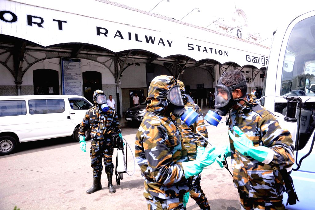 Sri Lanka Air force personnel put on protective equipment before disinfection operation in front of the Fort Railway Station in Colombo, Sri Lanka, March 18, 2020. ...