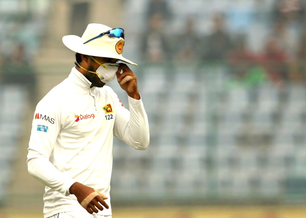 Sri Lanka's Dinesh Chandimal adjusts his anti-pollution mask during Day 4 of the third test match between India and Sri Lanka at Feroz Shah Kotla Stadium in New Delhi on Dec 5, 2017.