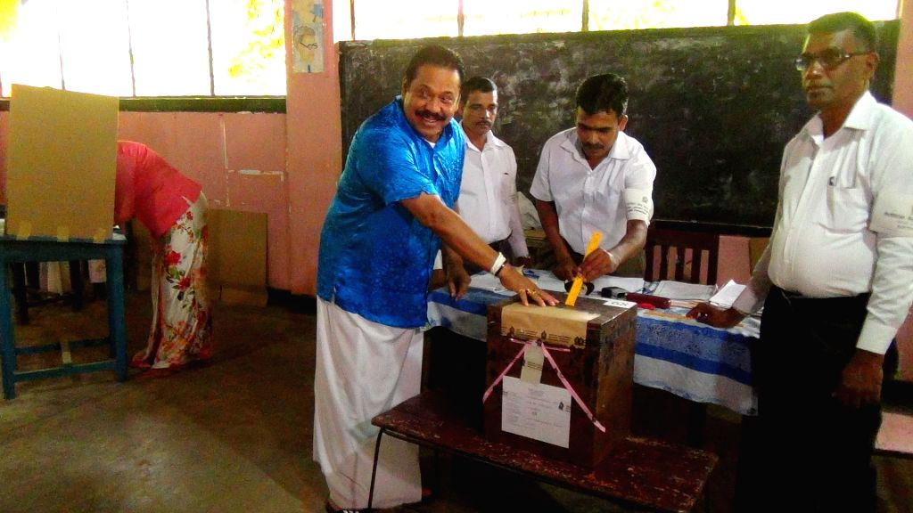 Sri Lankan former president and candidate of the opposition United People's Freedom Alliance (UPFA) Mahinda Rajapakse (1st L) votes at a polling station in ...