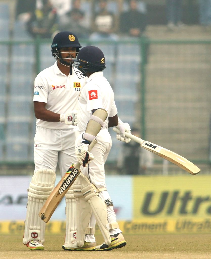 Sri Lankan skipper Dinesh Chandimal celebrates his one fifty run (150) with Lakshan Sandakan on Day 4 of the third test match between India and Sri Lanka at Feroz Shah Kotla Stadium in New ...