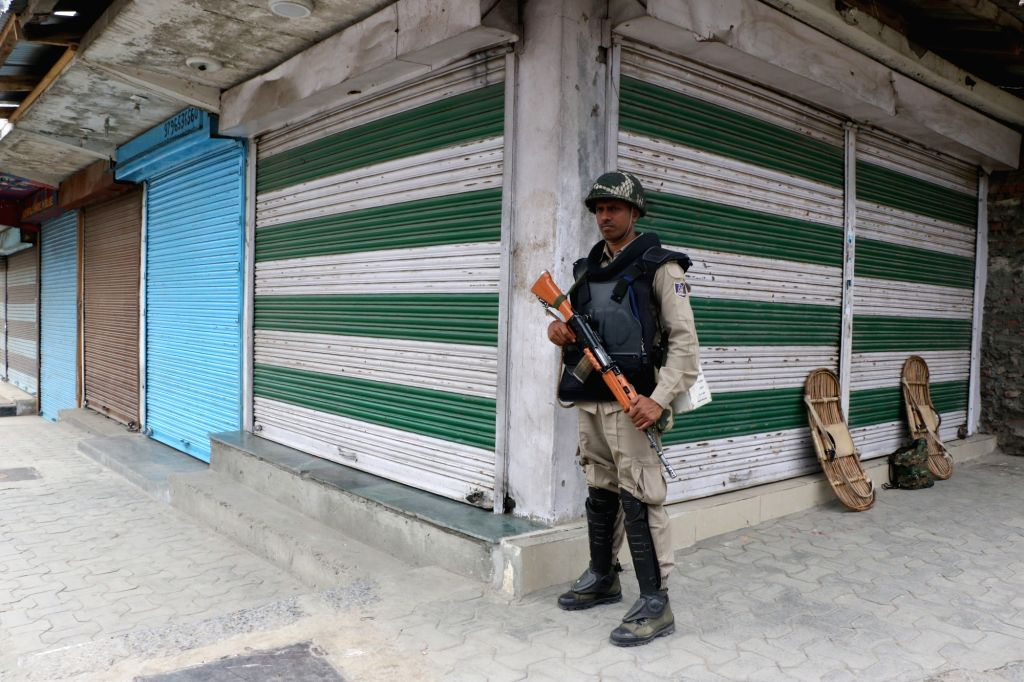 Srinagar: A security personnel stands guard as shops remain closed during a protest shutdown called by separatists across the Kashmir Valley; in Srinagar on July 11, 2018. Joint Resistance Leadership (JRL), separatist conglomerate headed by Syed Ali  - Malik