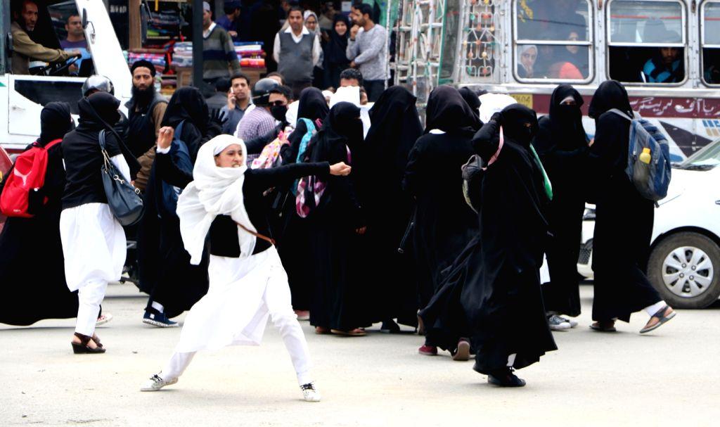 :Srinagar: An agitating student pelts stones on security personnel, in Srinagar on April 5, 2018. (Photo: IANS).