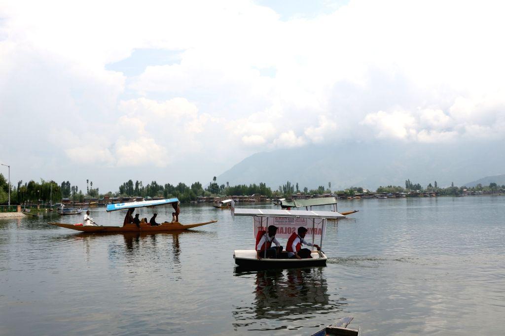 Srinagar: Jammu and Kashmir engineering students sail across the Dal Lake on a solar boat prepared by them, in Srinagar on July 21, 2018. (Photo: IANS)