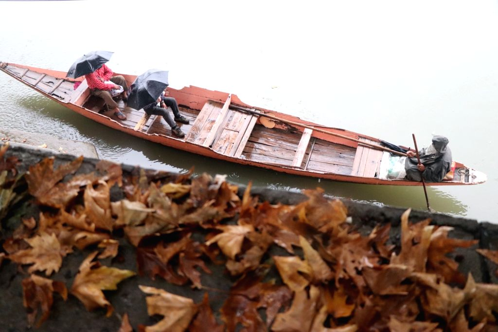Srinagar: People sail through a boat as they commute to their respective destinations on a rainy day in Srinagar on Aug 26, 2020. (Photo: IANS)