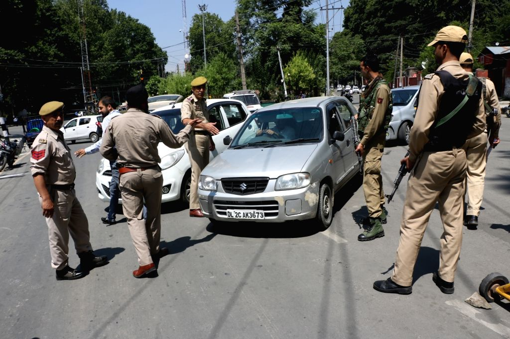 Srinagar: Police personnel frisking vehicles amid high security arrangements that have been made ahead of Union Home Minister Amit Shah's two-day maiden visit to Jammu and Kashmir, in Srinagar on June 26, 2019. (Photo: IANS) - Amit Shah