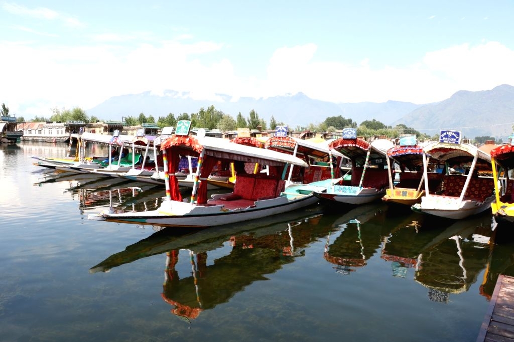 Srinagar: Shikaras anchored on the banks of Srinagar's Dal Lake as tourists leave Jammu and Kashmir after the Indian government advised Amarnath pilgrims and tourists to leave in view of the security situation. (Photo: IANS)
