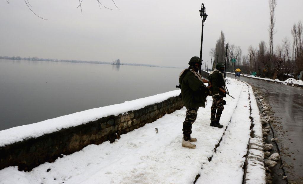 Srinagar: Srinagar: Security personnel stand guard on the banks of Dal Lake after snowfall in Srinagar, on Jan 20, 2019. (Photo: IANS)