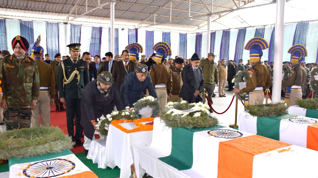 Srinagar: Union Home Minister Rajnath Singh lays wreath on the coffins of martyred CRPF soldiers, at the Regional Training Centre, in Srinagar on Feb 15, 2019. Also seen Jammu and Kashmir Governor Satya Pal Malik, Union Home Secretary Rajiv Gauba, CR - Rajnath Singh, Malik, Rajeev Rai Bhatnagar and Ranbir Singh