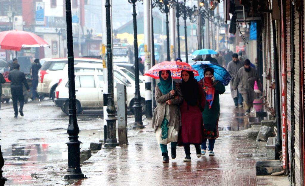 Srinagar: Women use umbrellas to protect themselves from rain in Srinagar on Jan 21, 2019. (Photo: IANS)