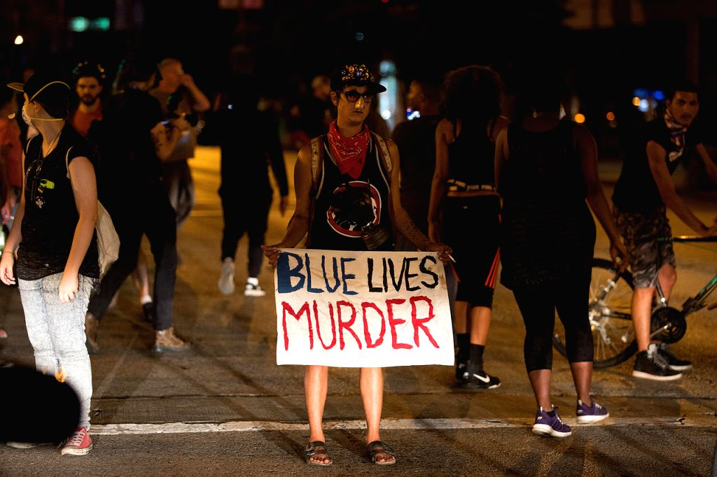 ST. LOUIS (U.S.), Sept. 18, 2017 A protester holds up a placard in St. Louis, Missouri, the United States, Sept. 17, 2017. Protesters smashed windows and other property in downtown St. ...