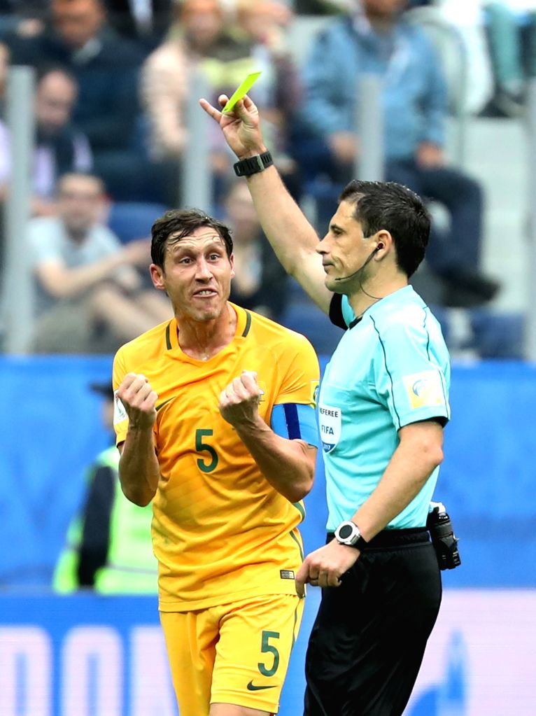 ST.Mark Milligan (L), capitain of Australia, expresses dissatisfaction as Serbian referee Milorad Mazic shows a yellow card to his teammate Bailey Wright during ...