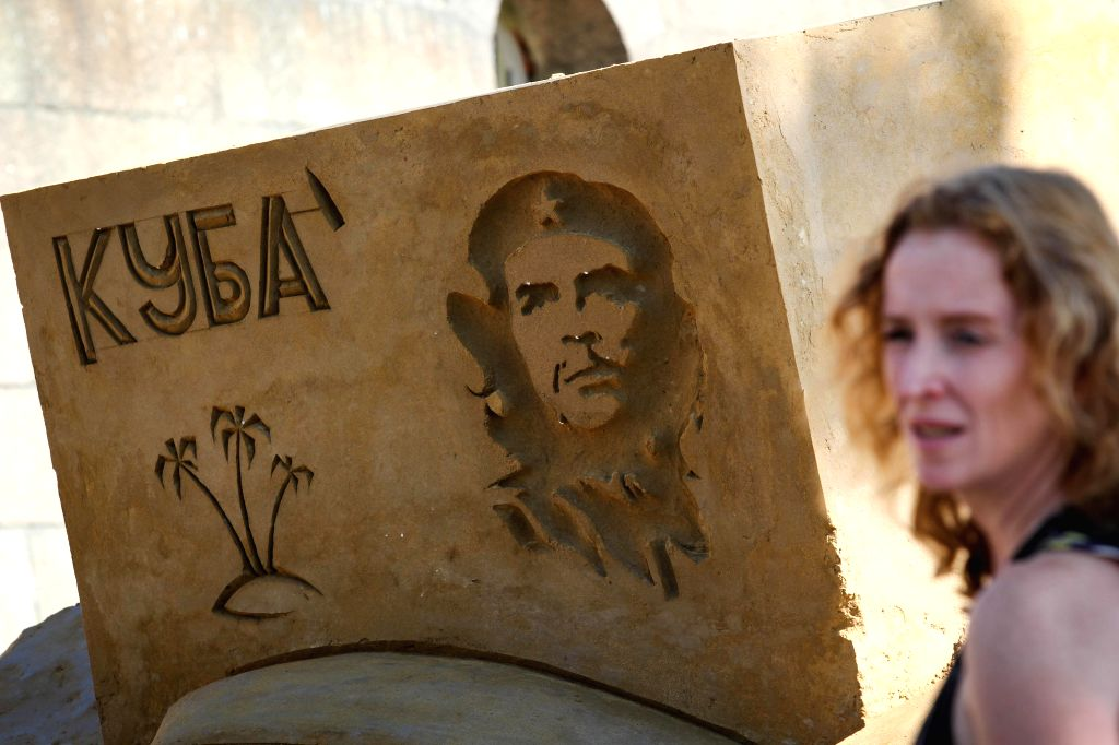 ST.A visitor walks past a sand sculpture displayed during the international festival of sand sculptures in St.Petersburg, Russia, on July 17, 2014. ...