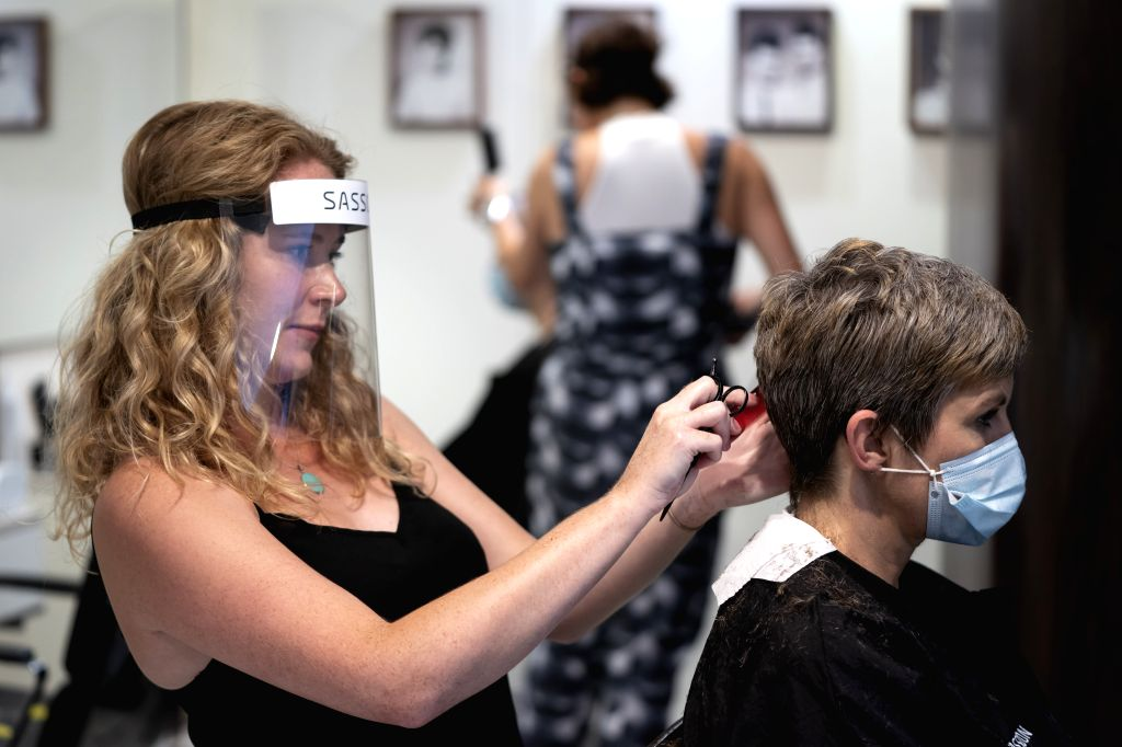 Staff Ashley Tonge (L) wearing personal protective equipment practices haircut on her colleague Pippa Marland for the reopening of Sassoon's Salon in Manchester, ... - Boris Johnson