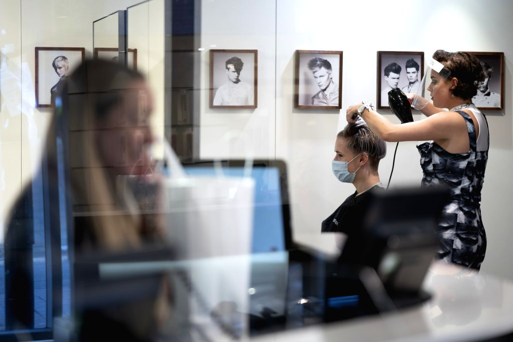 Staff Lizzie Lever (R) wearing personal protective equipment practices hair dressing on her colleague Nathan Tanner for the reopening of Sassoon's Salon in ... - Boris Johnson