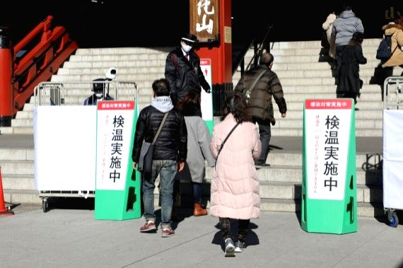 Staff members check the body temperature of visitors in front of Senso-ji temple at the sightseeing spot in Asakusa, Tokyo, Japan, Jan. 9, 2021.