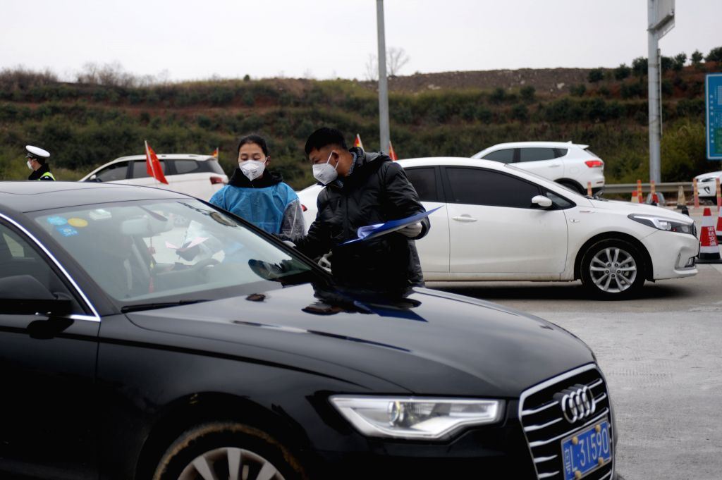 Staff members distribute leaflets on the prevention and control of the novel coronavirus to drivers and passengers at the Xinhua exit of Louhuai Expressway in Xinhua ...