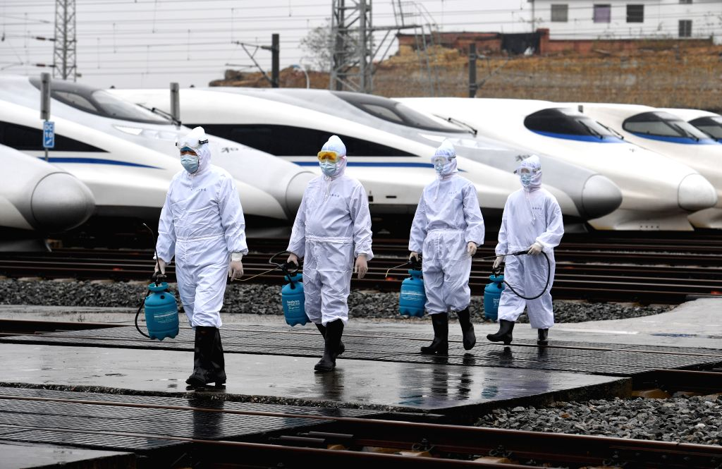 Staff members of China Railway Nanning Group Co., Ltd. walk out of bullet trains after disinfection work in Nanning, south China's Guangxi Zhuang Autonomous Region, ...