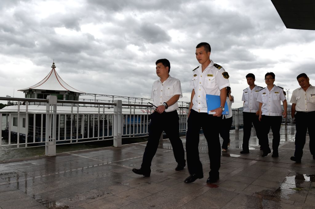 Staff members of local maritime safety bureau and ferry company examine a wharf in Xiamen City, southeast China's Fujian Province, Aug. 8, 2015. Affected by super ...