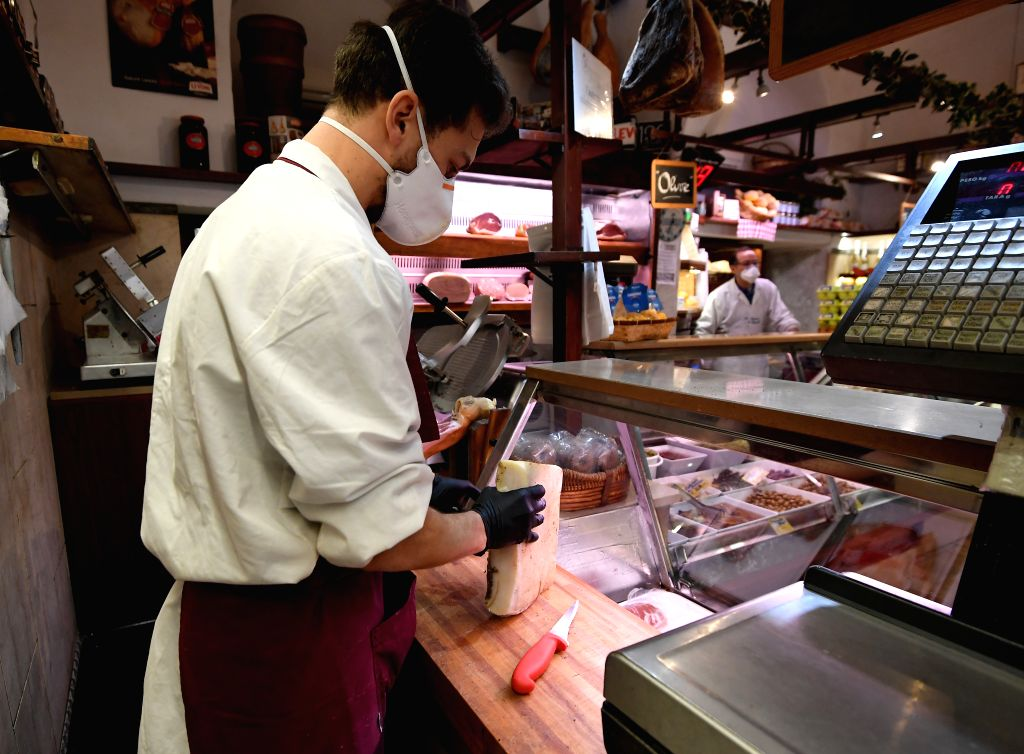 Staff members wearing face masks work in La Norcineria di Iacozzilli, a butcher shop in Rome, Italy, March 19, 2020. The cumulative number of those tested positive ...